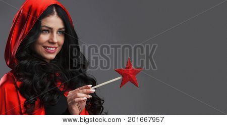 Gorgeous woman magician with star shaped magic wand poiting at copy space