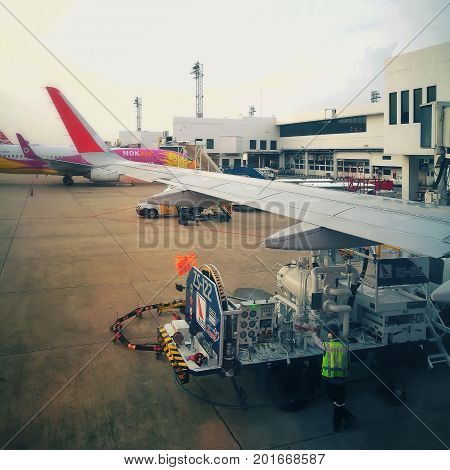 BANGKOK, THAILAND-MAY 20, 2017: Airport officer operate fuel truck to refuel an airplane at Don Mueang International Airport; use hose reel to dispense from hydrant pit (on floor) to target plane