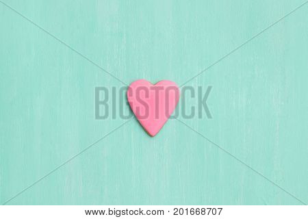 Top view on a pink gingerbread cookie in shape of heart on turquoise background. Flay layout. Love Valentines's day concept