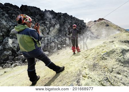 AVACHA VOLCANO KAMCHATKA PENINSULA RUSSIAN FAR EAST - AUG 7 2014: Two young women tourists photographed on smartphone on background of sulfur fumarole field in crater of active Avachinsky Volcano.