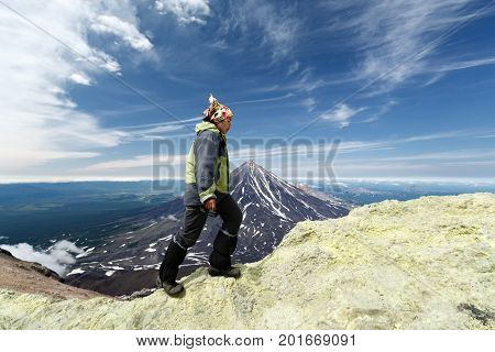 AVACHA VOLCANO KAMCHATKA PENINSULA RUSSIAN FAR EAST - AUG 7 2014: Young women tourists climb to sulfur fumarole field in crater of active Avachinsky Volcano on background of cone of Koryak Volcano.