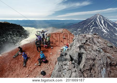 AVACHA VOLCANO KAMCHATKA PENINSULA RUSSIA - AUG 7 2014: Large group of happy and cheerful tourists and travelers in summit crater of active volcano after hours of climbing to the top of volcano.