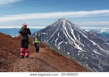 AVACHA VOLCANO KAMCHATKA PENINSULA RUSSIA - AUG 7 2014: Two young women tourists are walking along a mountain hiking trail on edge of crater of active volcano and photographing volcanic landscape.