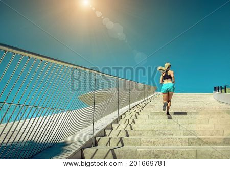 Blonde woman running training near the modern architecture building. Sport. Run. Blue sky. Sunny day. Summer. Training in urban place. City. Vacation. White stone building.