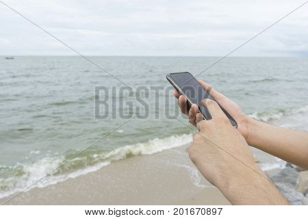 A Man Texting Cellphone On The Beach
