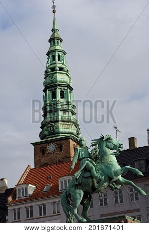 COPENHAGEN, DENMARK - NOVEMBER 7, 2016: Equestrian statue of Absalom against the tower of St. Nikolaj Church. Originated in 1200s, this city's 3rd oldest church now houses the Contemporary Art Center