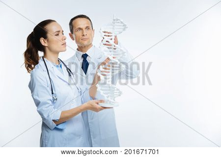 Future innovations. Selective focus on a mature male doctor standing next to his female colleague and touching a three dimensional dna model over the background.