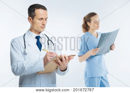 Not to forget. Waist up shot of a mature physician focusing his attention on a note book while holding a pencil and writing something down with a female coworker in the background.