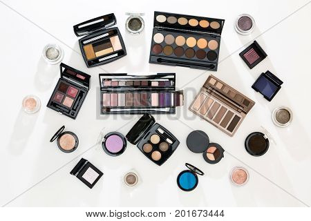Top view of different palettes of eye shadow on white.
