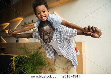 African American Father Piggybacking Son