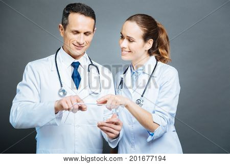 Waist up shot of two practitioners with stethoscopes enjoying their company while cooperating and using an invisible technological device together.