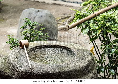 Water Spout and Stone at Buddhist Temple in Kyoto Japan