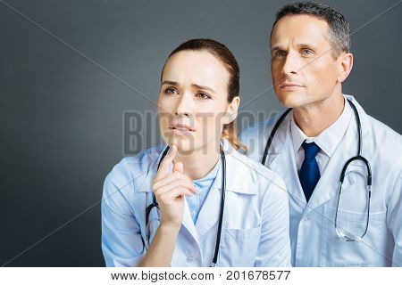 What should we do. Portrait of serious medical workers standing next to each other and pretending to look at an invisible screen while working together.