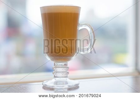Coffee latte with foam on the table restaurant window