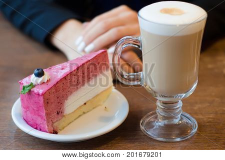Young beautiful woman drinks coffee latte with foam on the table cake restaurant