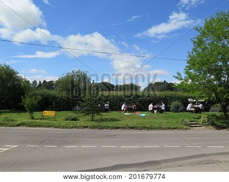 Aldworth England - August 5 2017: People enjoying lunch grass verge across from 17th century pub in Berkshire England