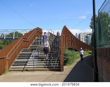People Climbing Steps To Modern Foot Bridge