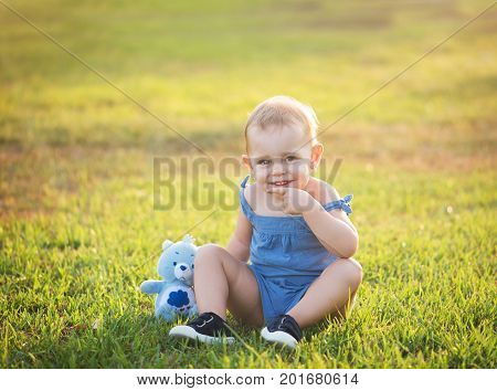 cute little girl is sitting on the grass in a park with a stuffed toy