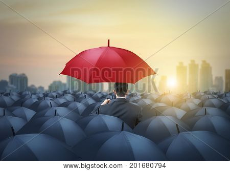 unique red umbrella among black umbrellas with city background