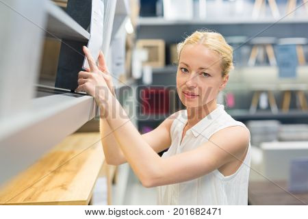 Caucasian woman shopping for furniture, recliner and home decor in store.