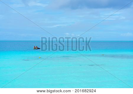 Romantic couple steering paddleboat on the crystal clear turquoise sea in the beautiful day at Maldives Island