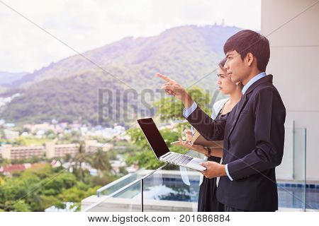 Young Asian Businessman Standing At The Terrace Looking To Building And Property. Used For Real Esta