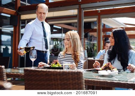 Expensive restaurant. Professional skillful nice waiter holding a bottle and pouring wine while serving customers