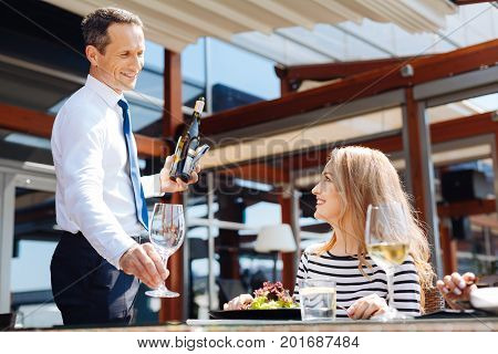 Restaurant service. Cheerful professional nice waiter putting a glass on the table and looking at his customer while preparing to pour wine