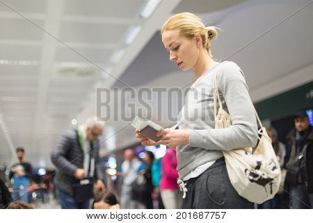Casualy dressed woman checking flight informations on airplane ticket while waiting for her flight at airport.