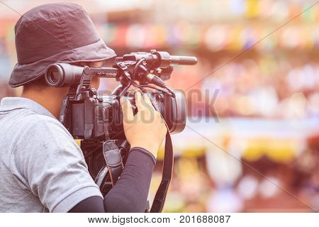 Cameraman Using Professional Digital Video Camera. Outdoor Setup And Working