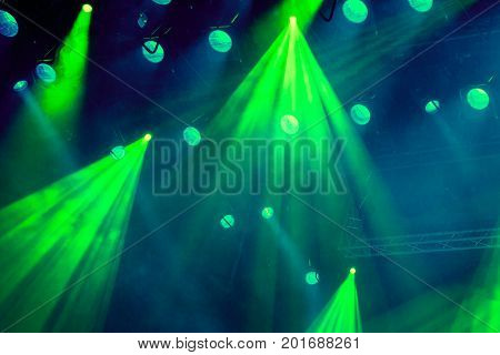 Lighting equipment on the stage of the theatre during the performance. The light rays from the spotlight through the smoke. Green rays of light