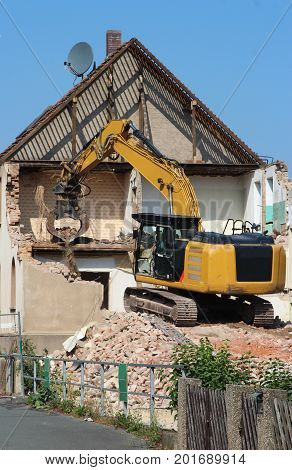 demolition of an old house with a chain excavator half done