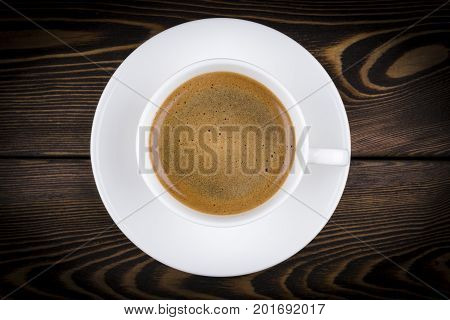 Overhead view of a freshly brewed mug of espresso coffee on rustic wooden background with woodgrain texture. Coffee break style