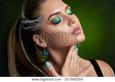 Attractive brunette girl  after beauty salon posing at studio with closed eyes, long eyelashes, makeup in green colors. Beautiful woman with rounded earring , shiny manicure touching neck and chin.