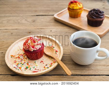 Red cupcakes put on a spherical wooden plate. Beside of cupcake have white coffee mug.In the background have yellow cupcake and chocolate cupcake.All of it rests on wooden table.