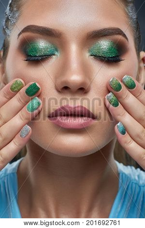 Front view of attractive brunette woman with perfect bronze skin, shiny manicure, makeup in green colors. Beautiful girl with plump lips, carried skin, touching showing nails. Beauty concept.