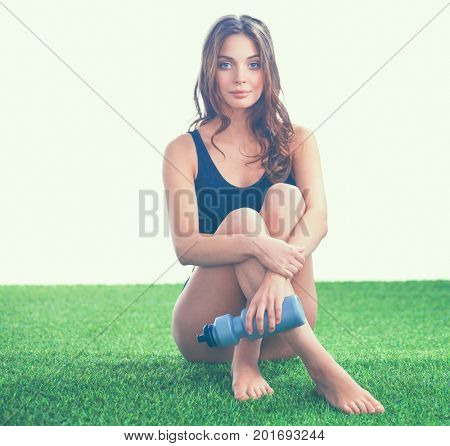 Woman sitting with crossed legs on the green grass