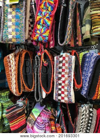 Assorted woolen head bands are hanging on display.