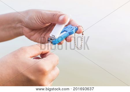 Close up woman cutting her nails using nail clipper