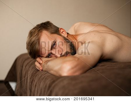Portrait of young man topless lying on bed with brown bedsheet .