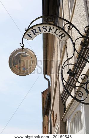 Guild sign for a hairdresser in the old town of Tangermuende in Germany
