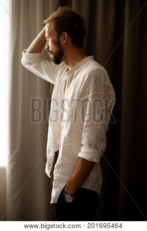 Young man in white unbuttoned shirt stands and looks in window.