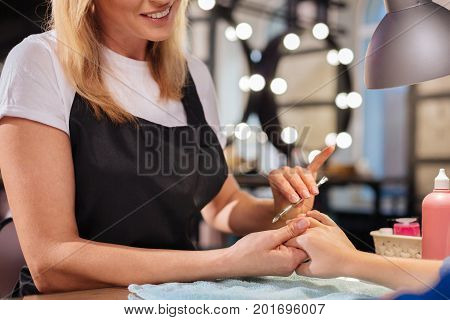 Gentle care. The close up of dainty hands of a young fair-haired manicurist holding a nail cleaner and being about to clean the nails of her client