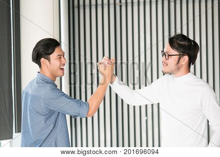 Portrait of a happy young man in office clapping their hands ok gesture asian smart handsome people.