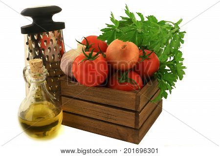 Colorful fresh ingredients seasoning and tool for cooking tomato souse. Organic tomatoes garlic onion plain parsley in wooden crate olive oil handhold kitchen shredder over white background