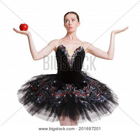 Graceful ballerina in black holding red apple in one hand showing other hand empty, isolated on white. Slimming and weight loss concept, copy space