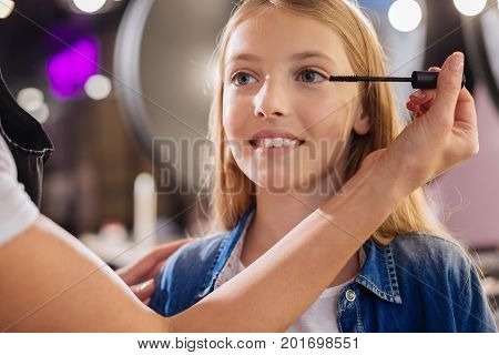 Top-notch service. The close up of delicate hands of a young makeup artist applying mascara to the eyelashes of a beautiful teenage girl sitting in a beauty salon