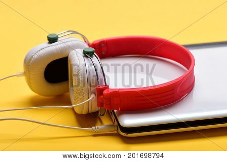 Electronics isolated on orange background. Earphones in red and white colors made of plastic with computer. Music and digital equipment concept. Headphones and silver laptop. Sound recording idea