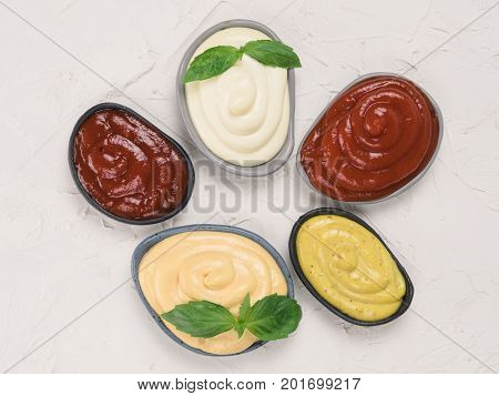 Top view of classic sauces set in trendy plates on white concrete background. Sauces set - salsa, mustard, ketchup, mayonnaise, cheese sauce, and basil for serve. Flat lay.