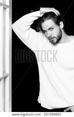 handsome bearded man or guy with beard on face in white sweater with raised hand on black background near wooden door